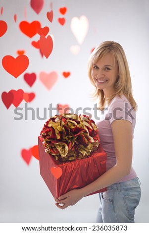 Young attractive girl with a gift and hearts - stock photo