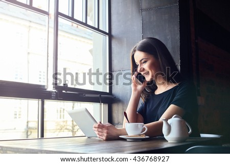 Young attractive girl with cute smile talking on mobile phone while sitting alone in coffee shop during free time and working on tablet computer. Happy female having rest in cafe. Lifestyle, coffee - stock photo