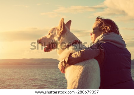 Young attractive girl with her pet dog at a beach, colorised image - stock photo