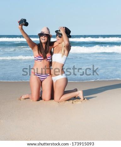 Young attractive girls beach self portrait camera - stock photo