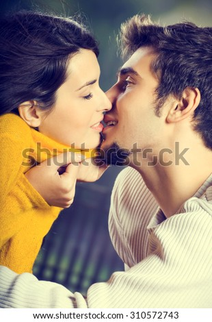 Young attractive happy amorous couple kissing outdoors - stock photo