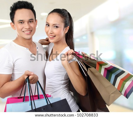 young attractive happy couple at shopping mall - stock photo