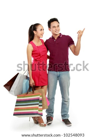 young attractive happy couple carrying shopping bag pointing to something - stock photo