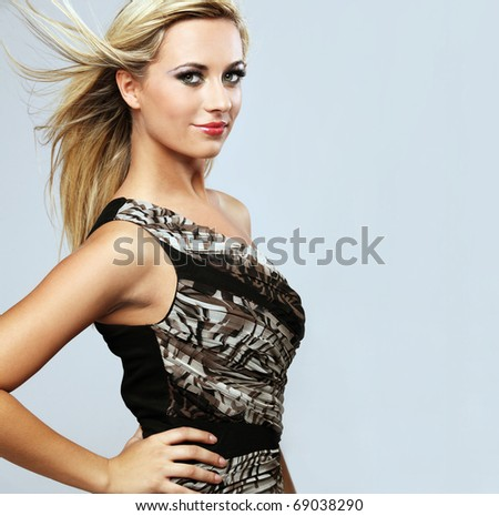 Young attractive happy fashion model witj long hair posing in studio. - stock photo