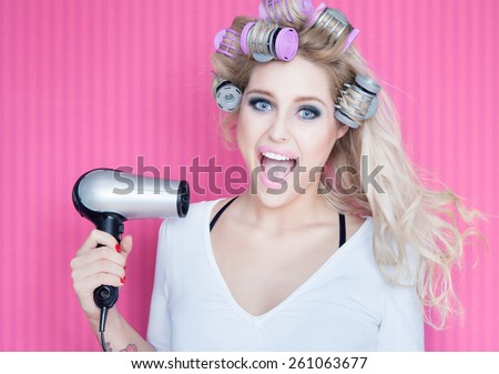 Young attractive happy laughing blonde woman with hair dryer and rollers - stock photo