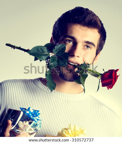 Young attractive happy man with gifts and rose, isolated on white background - stock photo