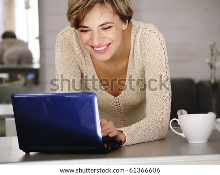 Young attractive happy smiling woman writing message on laptop - stock photo