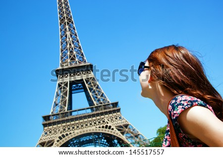 Young attractive happy woman looking at Eiffel Tower in Paris, France - stock photo