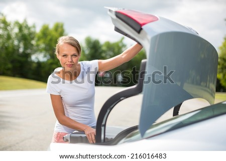 Young, attractive, happy woman taking a suitcase from her car's trunk, smiling, enjoying the travel experience - stock photo