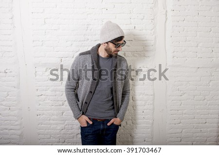 young attractive hipster and trendy style looking man posing cool with attitude dressing informal wearing casual beanie beard and sunglasses in male fashion concept - stock photo