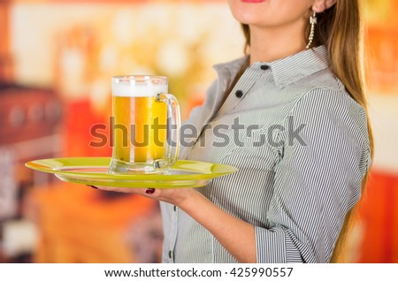 Young attractive holding a beer in bar,  close up - stock photo