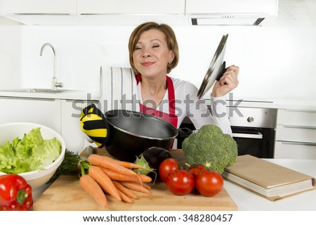young attractive home cook woman in red apron at domestic kitchen holding cooking pot with hot soup smelling delicious vegetable stew smiling satisfied in lifestyle and amateur cooking success - stock photo