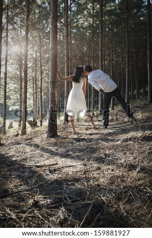 Young attractive indian couple flirting in the forest wearing white - stock photo
