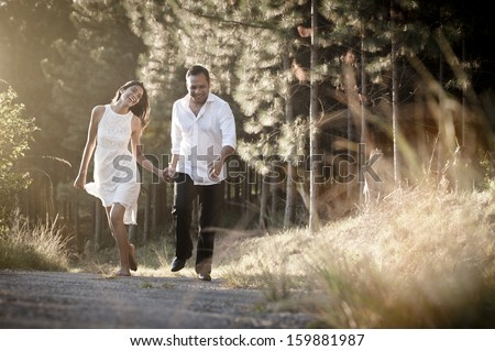 Young attractive indian couple strolling through a field - stock photo