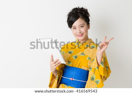 young attractive Japanese woman in a Yukata  to see a tablet computer - stock photo