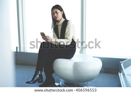 Young attractive Japanese woman is checking the status of account by using on-line internet banking on mobile phone. Asian female is waiting for car in airport, what she ordering on-line for the trip - stock photo