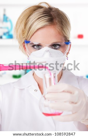 Young attractive laboratory assistant pouring chemical liquid into glass tube - stock photo