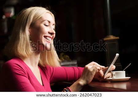 Young attractive lady at bar talking on phone - stock photo