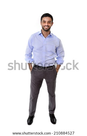 young attractive latin or spanish business man standing full body in corporate portrait isolated on white background smiling with hands in pockets wearing shirt and suit trousers - stock photo