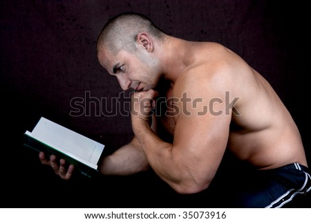 Young attractive male bodybuilder reading the book, pensive pose . Studio shot, dark background. - stock photo