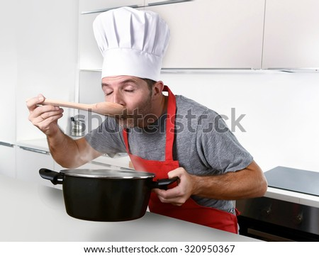 young attractive man in chef hat and red cook apron testing flavor while cooking soup holding pot with steam at modern home kitchen - stock photo