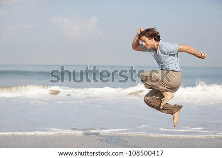 Young attractive man jumping by the sea shore while on vacation. - stock photo