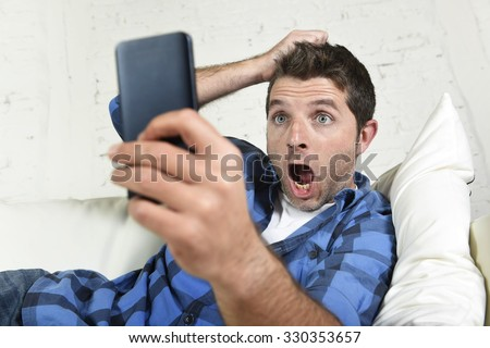 young attractive man lying at home couch using internet on his mobile phone looking surprised and shocked pulling hair in technology stress concept - stock photo