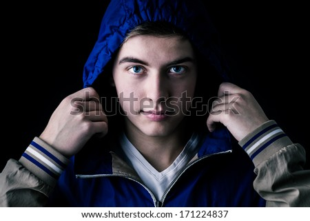 young attractive man pulling a hood over his head - stock photo