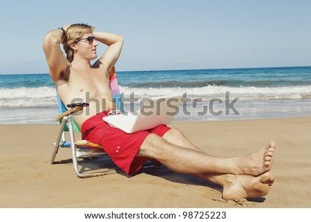 Young Attractive Man Relaxing at the Beach with Cell Phone and Computer - stock photo