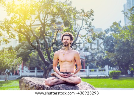 Young attractive man sitting in lotus position on a rock in the park and looks pensively to the side. - stock photo