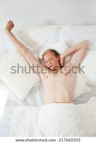 Young attractive man waking up in his bed - stock photo