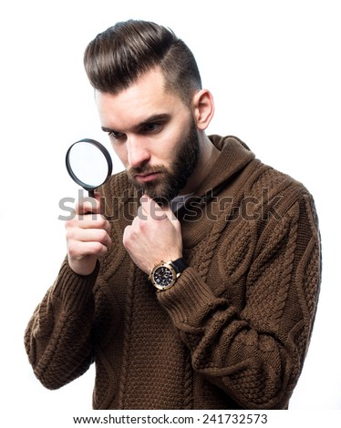 Young attractive man with a magnify glass against white background - stock photo