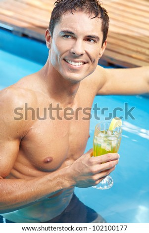Young attractive man with cocktail in a swimming pool - stock photo