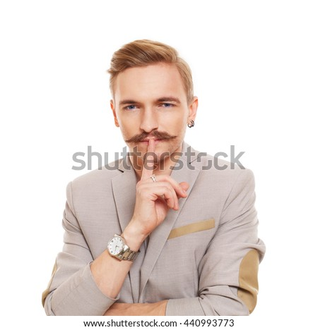 Young attractive man with mustache shows hush sign isolated at white. Handsome guy touch his lips with finger, secret ad mystery concept. - stock photo