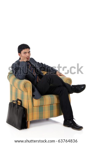 Young attractive nepalese businessman sitting on armchair, waiting. Briefcase beside. Studio shot, white background. - stock photo