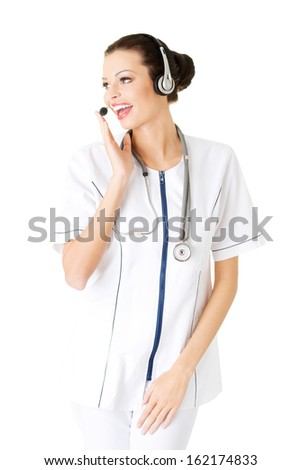 Young attractive nurde with stethoscope and headphones and microphone. Isolated on white.  - stock photo
