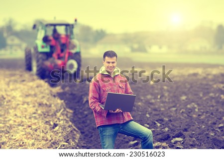 Young attractive peasant holding laptop in the field, tractor ploughing in the background - stock photo