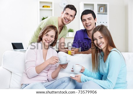 Young attractive people with drinks at home - stock photo