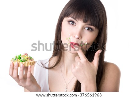 Young attractive playful hungry woman licking her covered in cream fingers while eating very tasty tart cake. Studio, white background, isolated - stock photo
