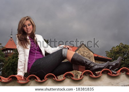Young attractive posing female dressed in violet vest and white jacket - stock photo