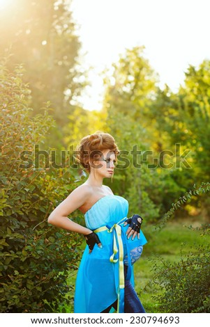 Young attractive pregnant girl with an unusual make-up walks in the park on a sunny day - stock photo