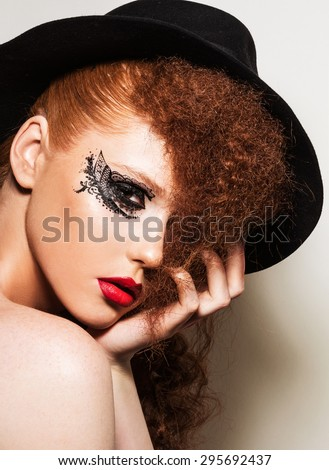 Young attractive red headed woman with creative makeup and hairstyle. Woman wearing classic black hat. Vogue style lace eye makeup. - stock photo