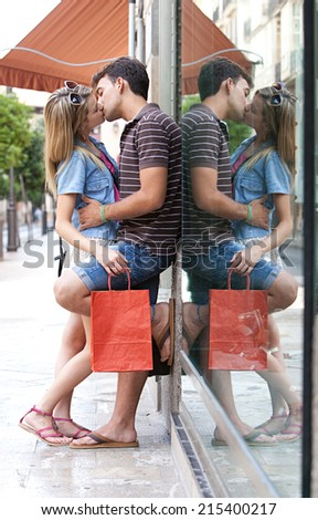 Young attractive romantic couple passionately kissing while shopping in a destination city while on holiday break, outdoors. Travel and lifestyle young people. - stock photo
