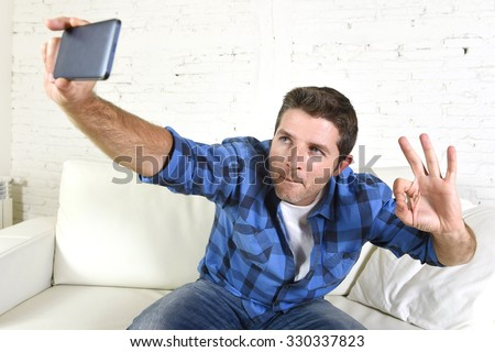 young attractive 30s man taking selfie photo or self video with mobile phone at home sitting on couch smiling happy giving thumbs up in use of technology and image concept - stock photo