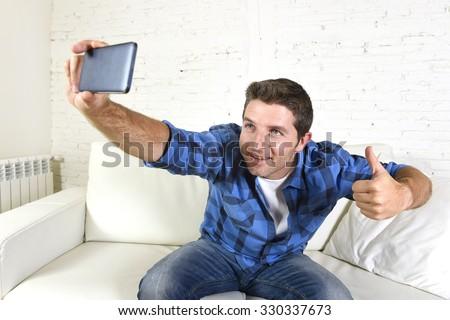 young attractive 30s man taking selfie picture or self video with mobile phone at home sitting on couch smiling happy giving thumbs up in use of technology and image concept - stock photo
