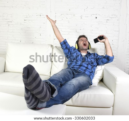 young attractive 20s or 30s man having fun alone lying on home couch listening to music holding mobile phone as microphone using headphones singing passionate happy and crazy - stock photo