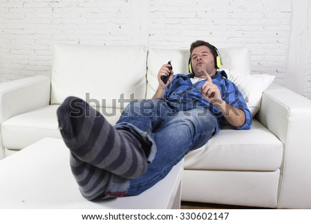 young attractive 20s or 30s man having fun alone lying on home couch listening to music with mobile phone and headphones following the rhythm  passionate happy and crazy - stock photo