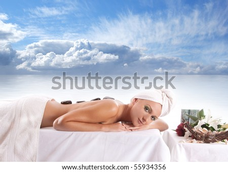 Young attractive sexy blond getting spa treatment over sea background - stock photo