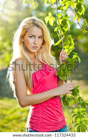 Young attractive sexy  girl with red shirt and blond hair outdoor on the field.Golden lady in autumn day - stock photo
