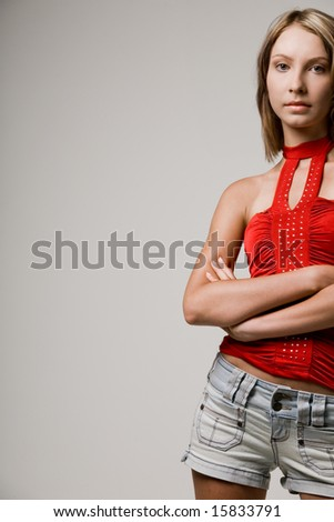 Young attractive slim fashion model in red shirt and shorts. - stock photo